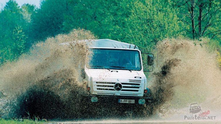 Белый Mercedes-Benz Unimog в брызгах грязи на дороге