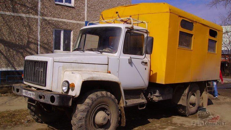 Белый грузовик вахтового типа с тёмно-жёлтой будкой