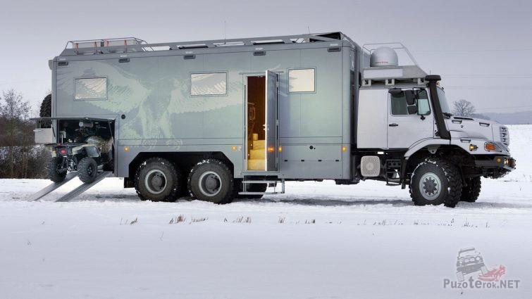 Большой автодом с выезжающим квадроциклом на снегу