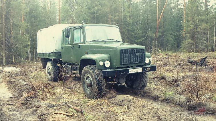 Бортовой грузовик болотного цвета на пересечённой местности