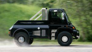 Чёрный грузовик едет по дороге