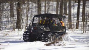 Чёрный снегоболотоход Арго с кабиной в зимнем лесу