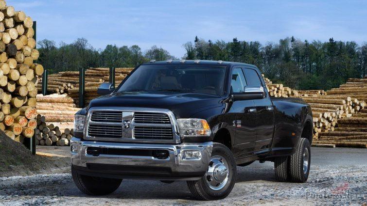 Чёрный стандартный Dodge Ram на фоне брёвен