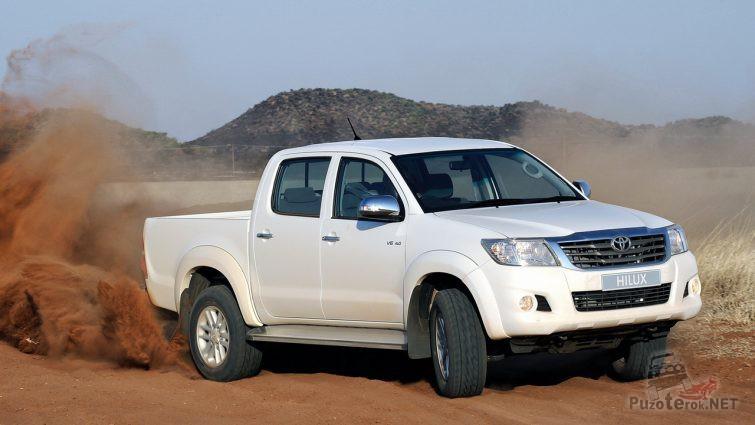 Дрифт белой Тойоты Хайлюкс на песчаной дороге