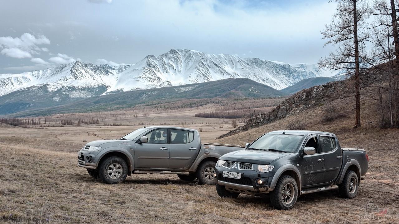 Два пикапа L200 на фоне снежных вершин
