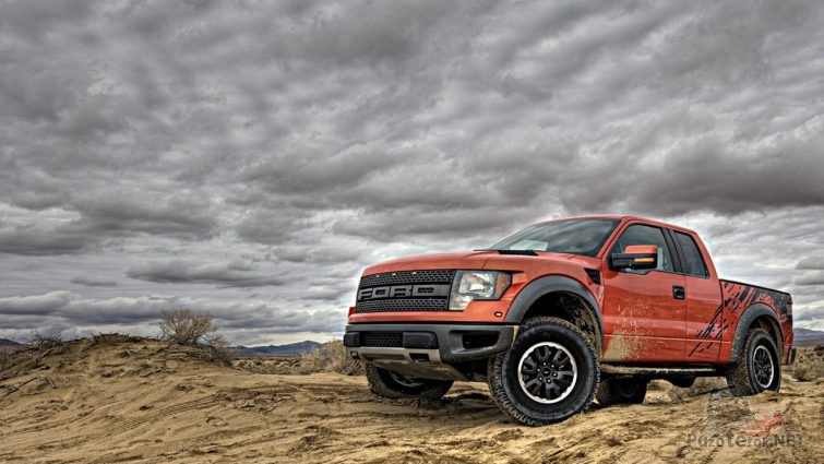 Ford Раптор на песке, на фоне облачного неба