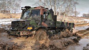 Грузовик цвета хаки на грязевой дороге