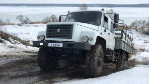 Грузовой автомобиль выезжает из грязи возле зимнего озера