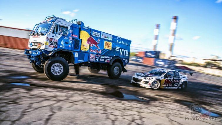 Камаз обгоняет гоночный автомобиль на трассе