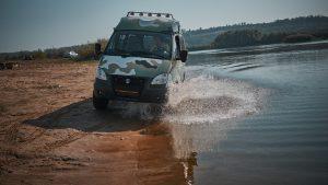 Камуфляжный Соболь 4x4 едет по берегу реки