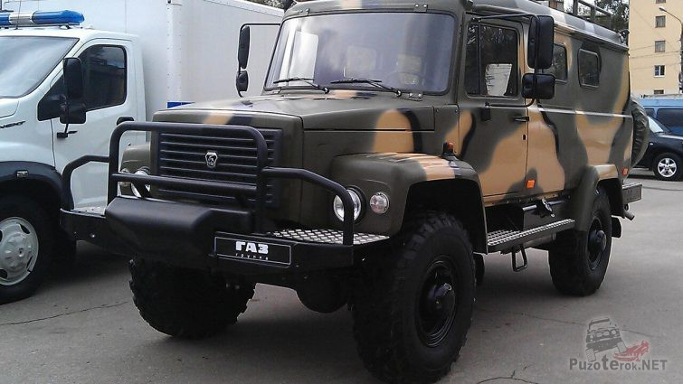 Камуфляжный грузовик рядом со служебной машиной на стоянке