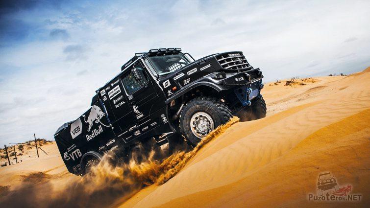 Капотный чёрный Камаз взбирается на песчаную гору в пустыне