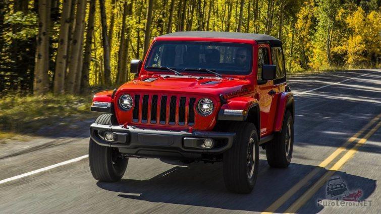 Красный Jeep Wrangler едет по шоссе в лесу