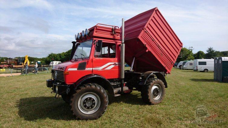 Красный Unimog с поднятым кузовом