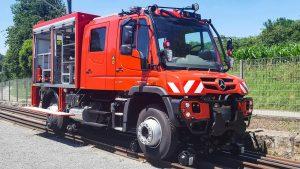 Красный локомобиль Mercedes-Benz Unimog на рельсах