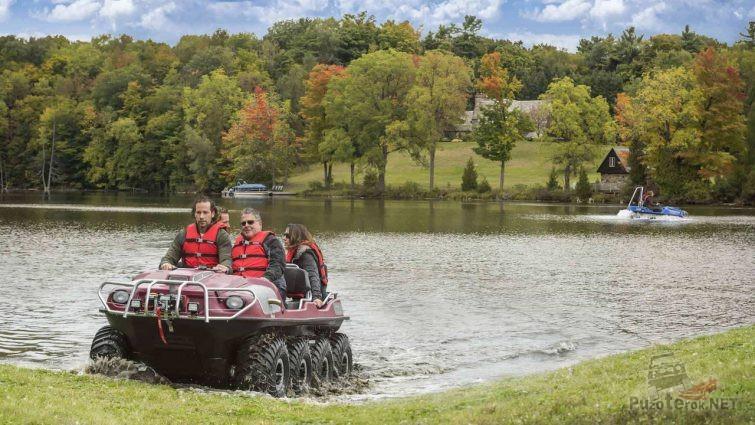 Красный вездеход с людьми выезжает из озера