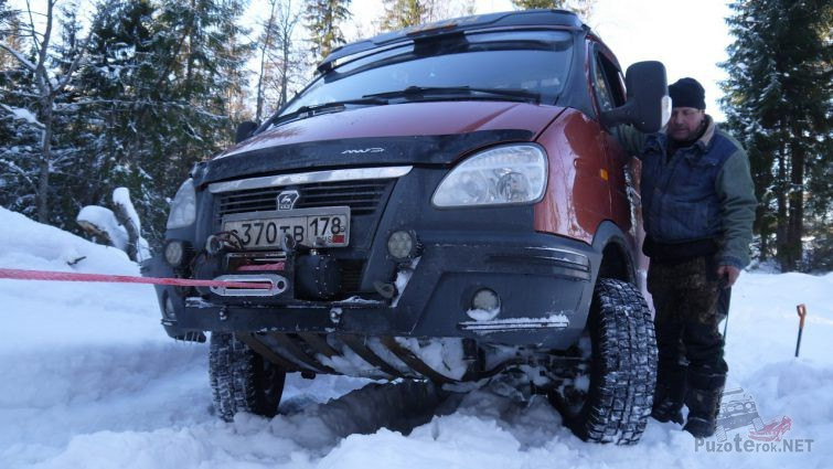 Красный внедорожник Соболь вытаскивают лебёдкой по снегу