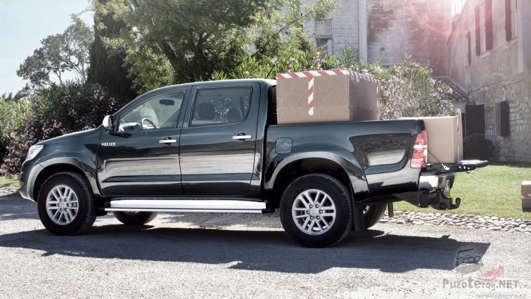 Кузов чёрного пикапа загружен коробками на улице