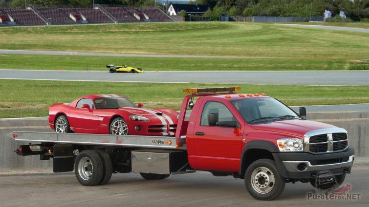 Маленький грузовичок везёт гоночную машину