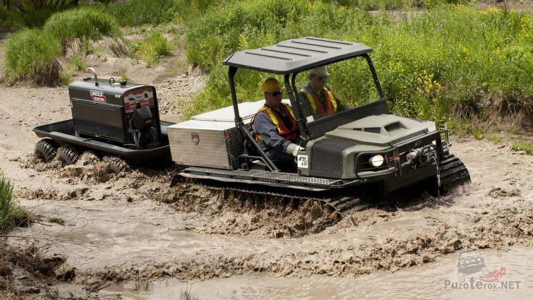 Мужчины на болотоходе с прицепом проезжают глубокую лужу
