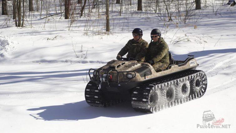 Мужчины в касках на гусеничном вездеходе зимой