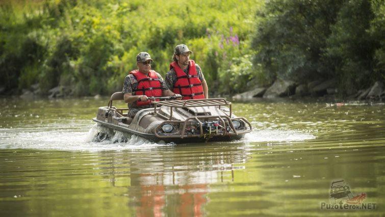 Мужчины в красных жилетах на вездеходе плывут по реке