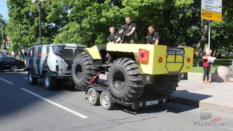 Мужчины в жёлтом вездеходе на буксире в городе