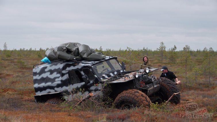 Мужчины возле завязшего вездехода в болотистой местности