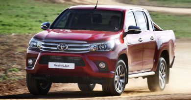 Новая красная Toyota Hilux на скорости за городом