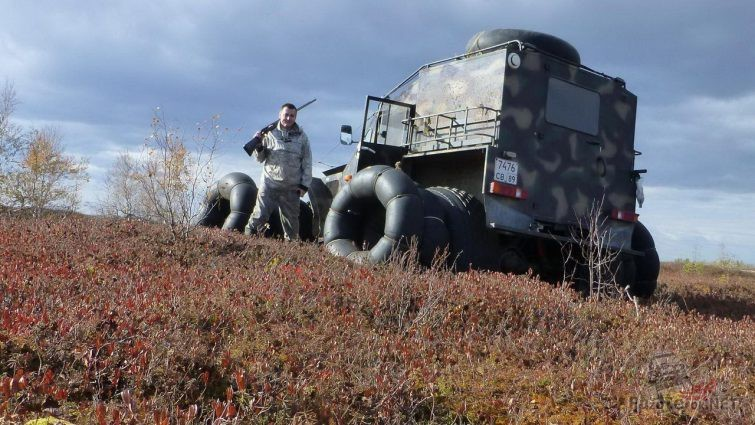 Охотник возле вездехода с добавленными шинами