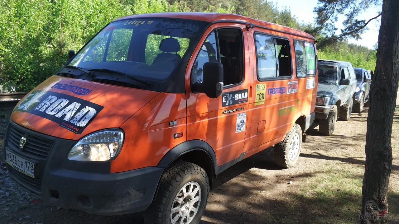 Оранжевый автомобиль Соболь едет по дороге с другими внедорожниками