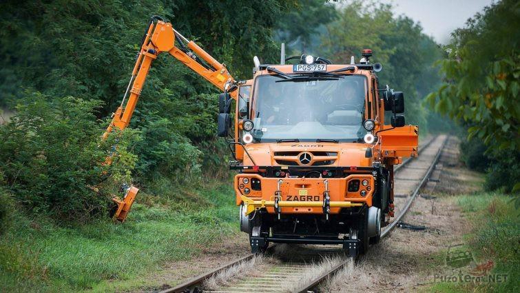 Оранжевый локомобиль срезает кусты