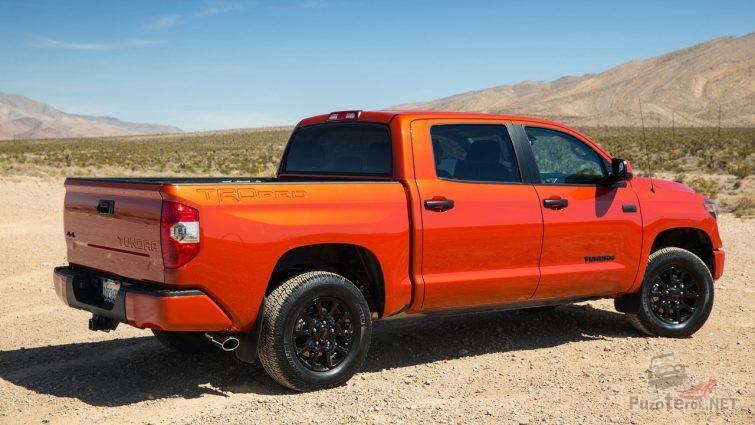 Оранжевый пикап с чёрными дисками на песчаной местности
