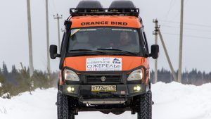 Оранжевый тюнингованный Соболь на зимней дороге