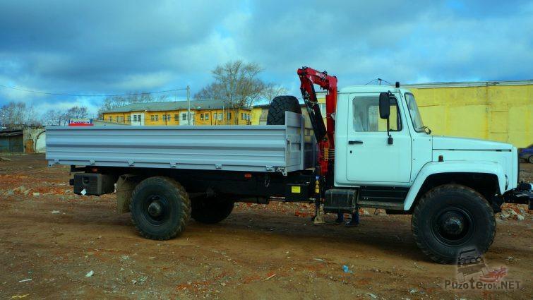 Оснащённый краном бирюзовый грузовик на улице