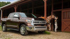 Пикап Тойота Тундра рядом с девушкой и лошадью