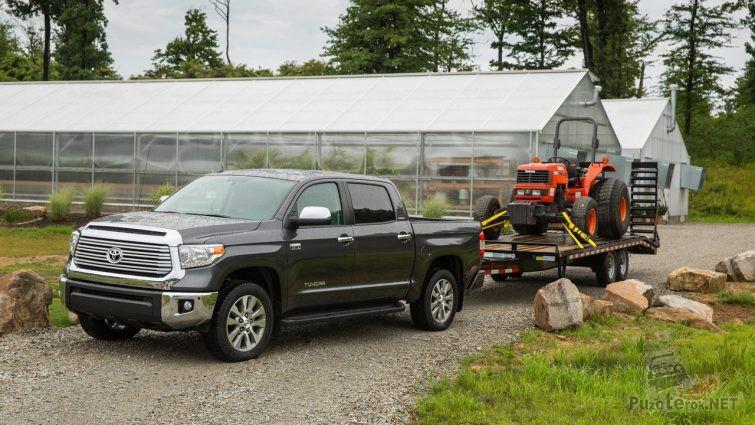 Пикап Toyota Tundra с маленьким трактором на прицепе возле теплиц