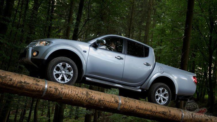 Пикап едет по связанным брёвнам в лесу