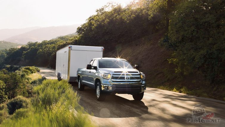 Пикап везёт прицепной фургон по дороге