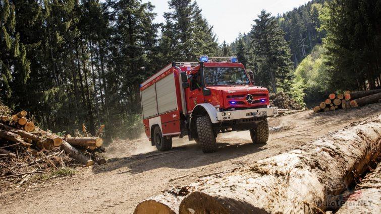 Пожарная машина на базе Унимога среди брёвен в лесу