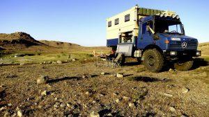 Путешественник отдыхает возле экспедиционного Mercedes-Benz Unimog