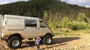 Ребёнок возле Соболя с большими колёсами на природе