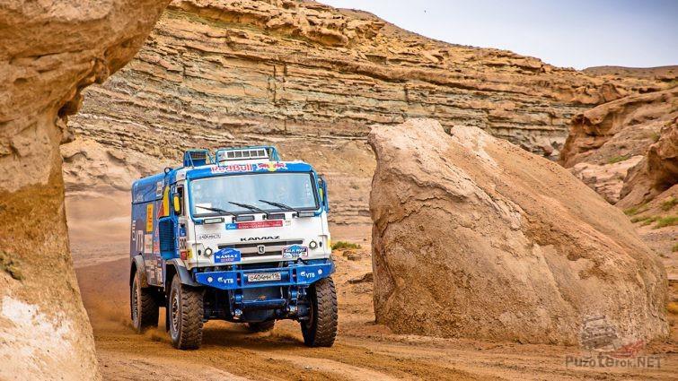 Российский грузовик едет между денудационных гор