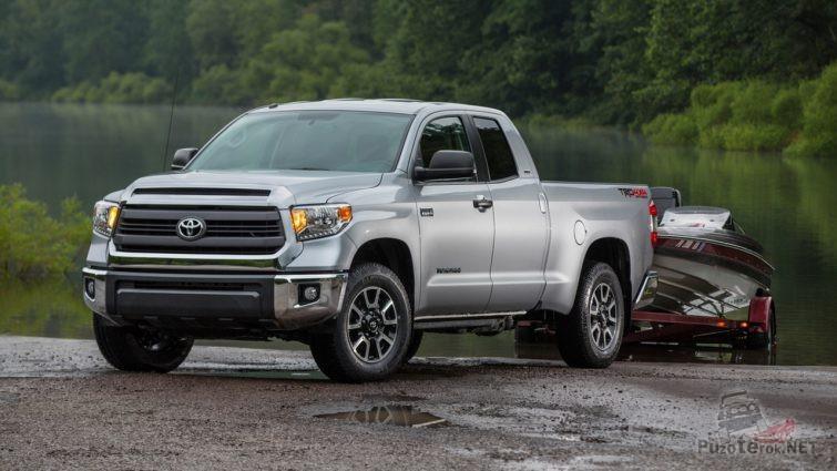 Серая Toyota Tundra на прицепе спускает катер в озеро