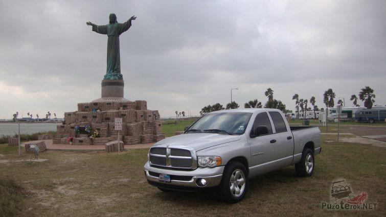 Серый Dodge Ram возле статуи Исуса