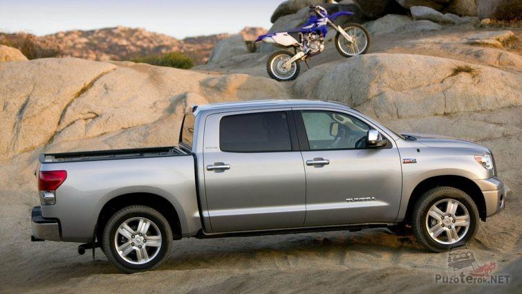 Серый пикап на песке с мотоциклом на заднем плане