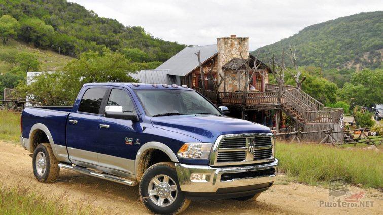 Синий Dodge Ram на сельской дороге у дома