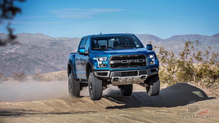 Синий Ford Раптор в прыжке с горки на дороге