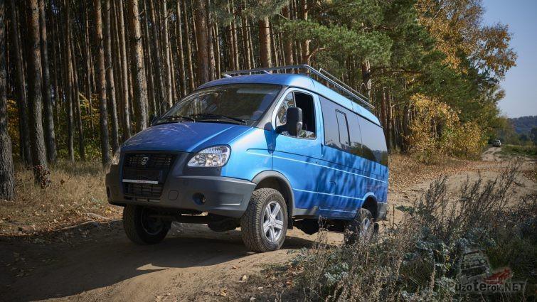 Синий ГАЗ Соболь взбирается на небольшую горку на дороге в лесу