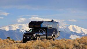 Синий джип с кунгом на фоне снежных гор
